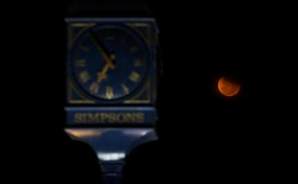A lunar eclipse is seen beside a clock tower at Marina Beach in Chennai, India, Saturday, April 4, 2015. (AP Photo/Arun Sankar K)