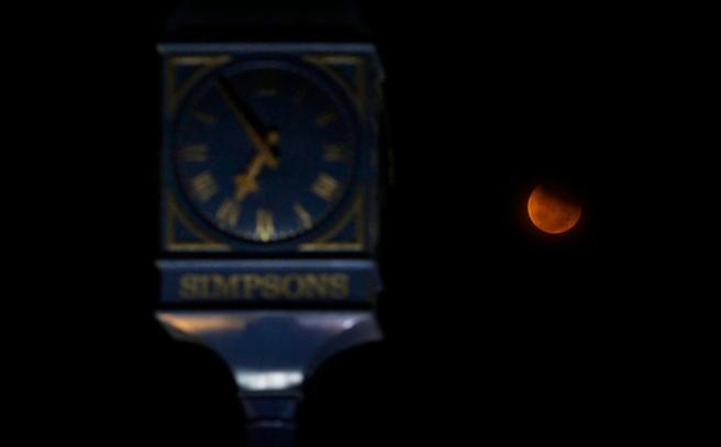 A lunar eclipse is seen beside a clock tower at Marina Beach in Chennai, India, Saturday, April 4, 2015. (AP Photo/Arun Sankar K)