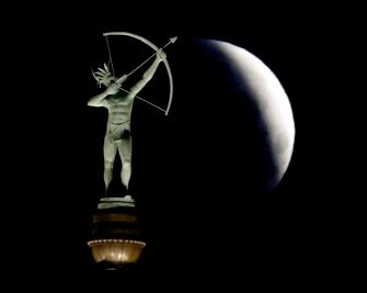 A partially eclipsed full moon sets behind a statue of a Kansa Indian at the Kansas Statehouse, Saturday, April 4, 2015 in Topeka, Kan. (AP Photo/Charlie Riedel)