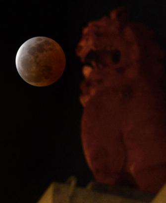 A lunar eclipse is observed above a lion-shaped statue in Urasoe city, Okinawa prefecture, southern Japan, Saturday, April 4, 2015. (AP Photo/Kyodo News) JAPAN OUT, MANDATORY CREDIT