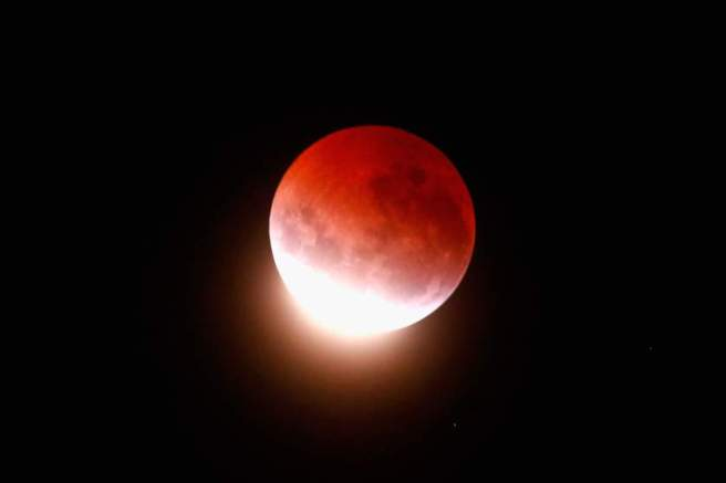 "AUCKLAND, NEW ZEALAND - APRIL 04: A blood red moon lights up the sky during a total lunar eclipse on April 4, 2015 in Auckland, New Zealand. The shortest total lunar eclipse, or ""blood moon"", of the century will last just a few minutes. (Photo by Phil Walter/Getty Images)"