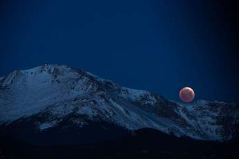 COLORADO SPRINGS, CO - APRIL 04: Sky-watchers got a glimpse of the Blood Moon in the shortest eclipse of the century as it sets behind Pikes Peak April 4, 2015 in Colorado Springs. The top edge of the eclipsed moon should appear much brighter than the rest of the orb.(Photo By John Leyba/The Denver Post via Getty Images)