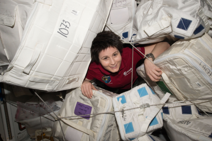 (05/04/2015) --- ESA (European Space Agency) astronaut Samantha Cristoforetti glides through supply containers packed onboard the International Space Station. (Flickr: nasa2explore)